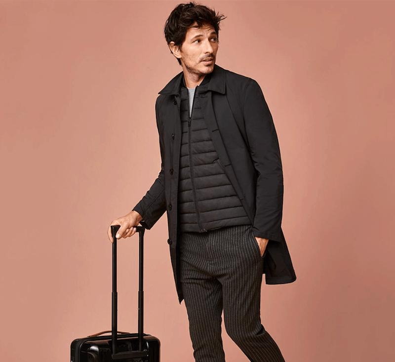 mann trägt eine anzughose sowie weste mit trenchcoat und schiebt einen koffer